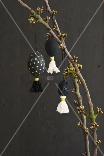 Easter decorations hung from branch against black background