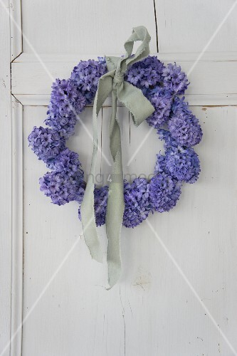 Wreath of blue hyacinths tied with pale fabric ribbon