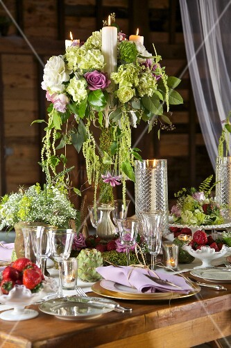Flowers and candles on festively set, rustic-style table