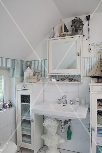 Maritimes Badezimmer mit weißen Schränkchen und einer Büste – Bild ...