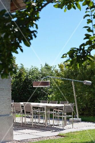 Modern standard lamp above table on sunny terrace