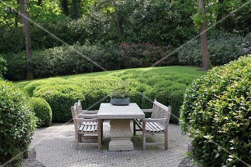 Seating area on terrace surrounded by bushes