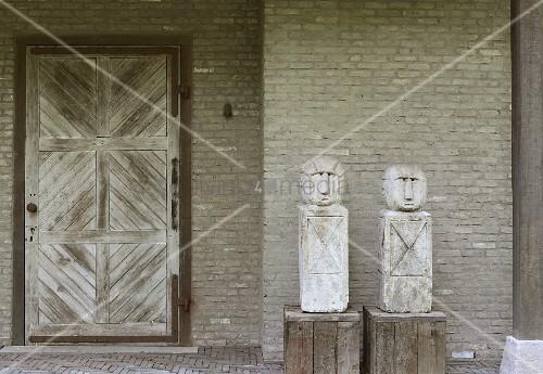 Zwei Figuren auf Holzsockeln vor Backsteinwand und Holztür