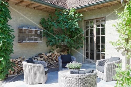 Gemütliche Sitzecke vor dem Haus mit grauen Korbsesseln