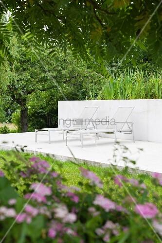 Sun loungers on concrete terrace in summery garden