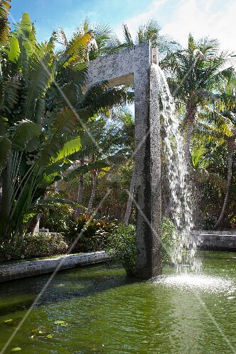 Waterfall falling into pool in tropical garden