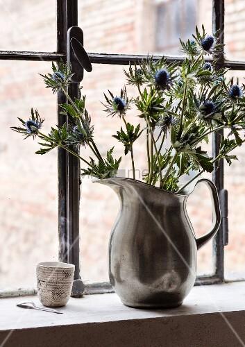 Fabrikfenster Kaufen blaue disteln in einer zinkkanne als vase vor einem fabrikfenster