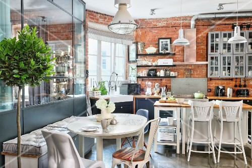 Mixture of industrial, vintage and modern styles in kitchen-dining room of loft apartment