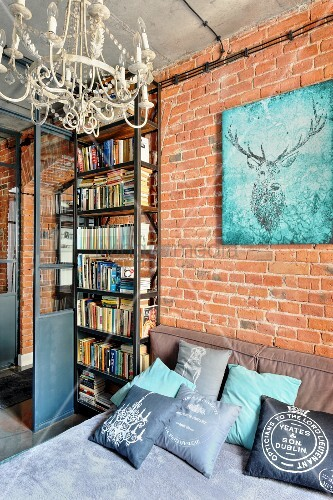 Picture of stag on brick wall above bed with many scatter cushions