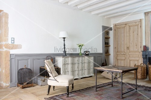 Pale easy chair, coffee table, vintage birdcage, stacked trunks and chest of drawers in living room
