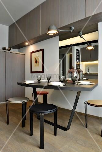 Minimalist dining area below wall-mounted cupboards