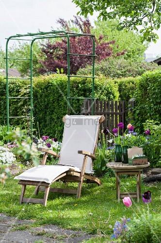 Wooden lounger, flowering tulips and trellis in garden