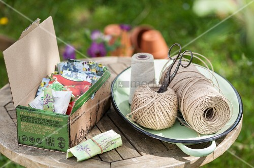 Various seed packets in cardboard box and twine on garden table