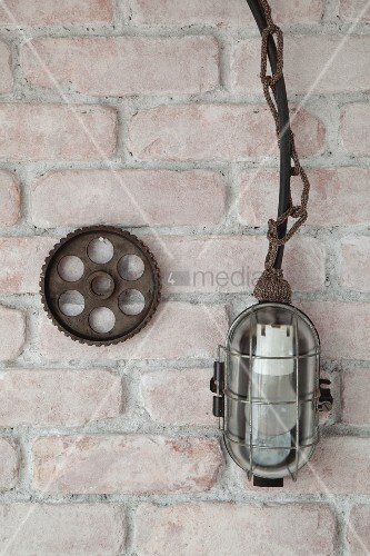 Cage lamp with knitted chain next to cog on brick wal