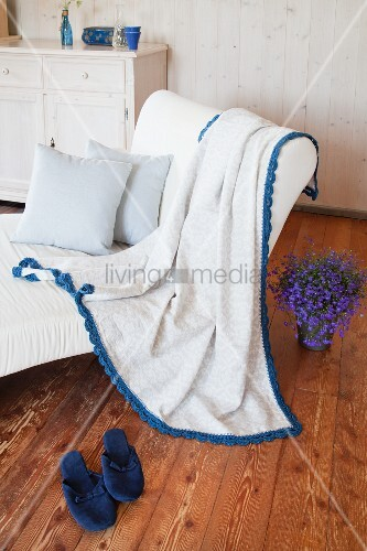 Blanket with blue crocheted trim on white armchair in rustic living room