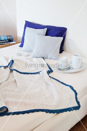 Blanket with blue crocheted trim and breakfast crockery on bed