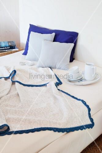 Decke mit blauer Häkelborte auf dem Bett mit Frühstücksgeschirr