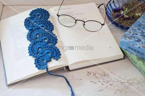 Blue crocheted bookmark and reading glasses on open book
