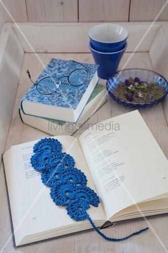 Blaues, gehäkeltes Lesezeichen im aufgeschlagenen Buch
