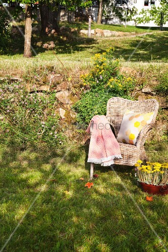Blanket and printed cushion on wicker armchair on lawn