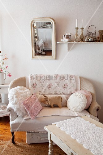 Cushions and fabric pig on sofa below shabby-chic mirror on wall