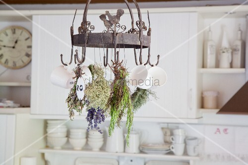 Cups and herbs hung from vintage metal rack