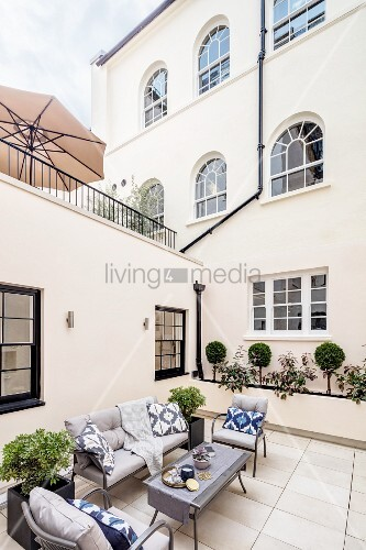 Seating area on terrace outside house with arched windows