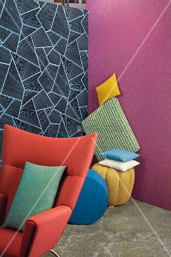 A red armchair and a pile of cushions in front of a two brightly coloured walls