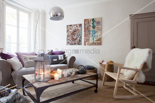 Arc lamp and rocking chair with sheepskin blanket in cosy, candlelit living room