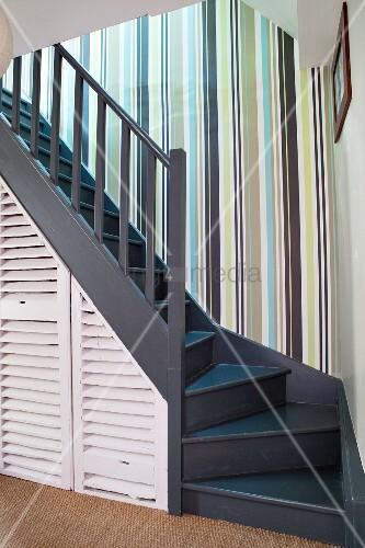 Treppenaufgang mit Streifentapete und Stauraumlösung unter Holztreppe