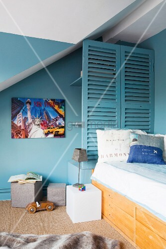 Petrol-blue walls and shelves behind slatted screen in boy's bedroom