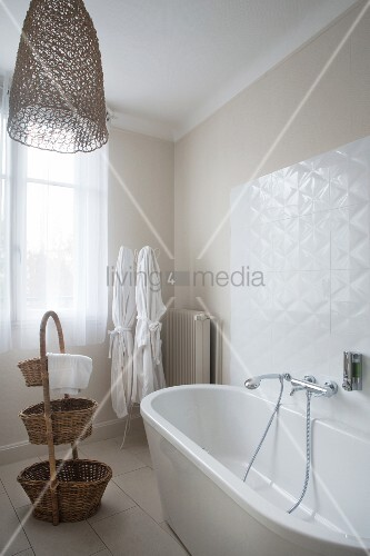 Free-standing white bathtub, dressing gowns and baskets in bathroom