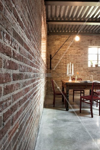 Candlesticks and laptop in illuminated dining area with brick walls