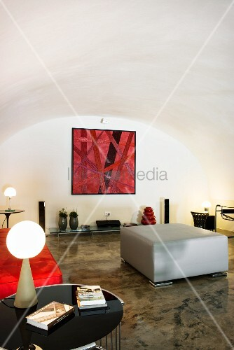 Restored white vaulted ceiling and glossy concrete floor in designer living area