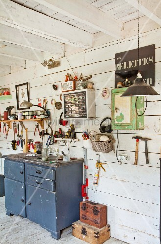 Various tools hung on wooden wall in workshop