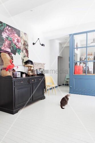 Cat, sideboard and feminine accessories in retro interior