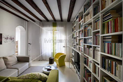 Large bookcase and wood-beamed ceiling in living room