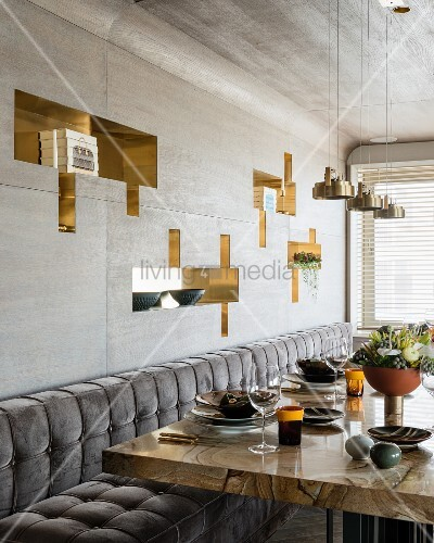 Set dining table with stone wood marble top below geometric niches with shiny linings in grey wood-clad wall