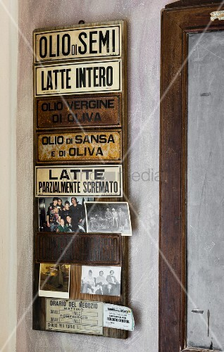 Italian signs and family photos on board on wall