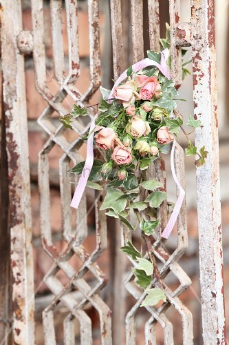 Romantic arrangement of pink roses and ivy on vintage lattice