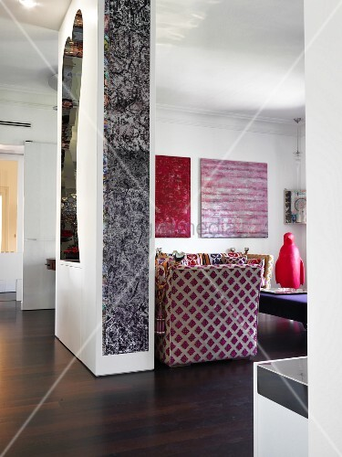 Modern artwork and mirror on partition wall with view into open-plan living area
