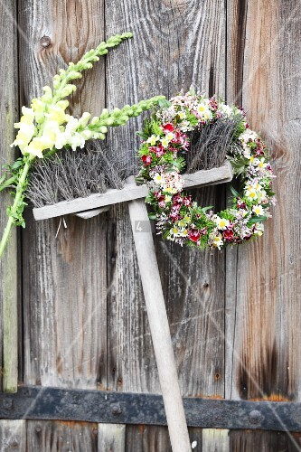Flower wreath and two snapdragons hung from broom