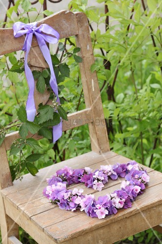 Hydrangea and phlox flowers arranged in love heart on old wooden chair