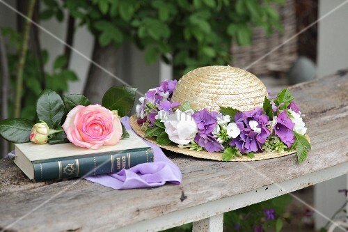 Straw hat with wreath of flowers next to rose on book in garden