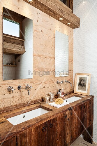 Rustic washstand and wood-panelled wall in ensuite bathroom