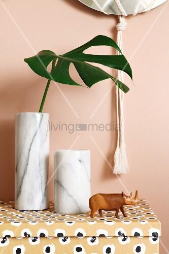 Marmorvase mit Monstera Deliciosa-Blatt neben geschnitzter Nashornfigur auf gemusterter Pappschachtel
