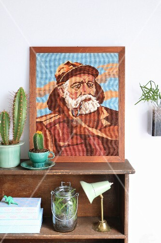 Embroidered portrait of fisherman and cacti on vintage-style wooden shelves