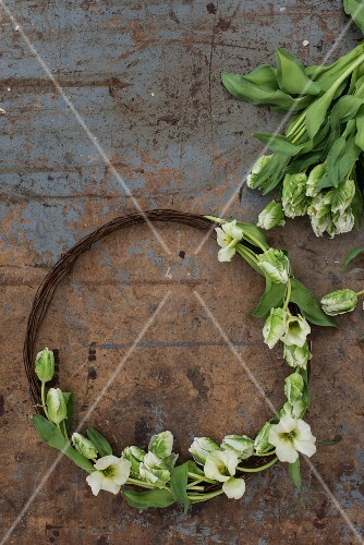 Rustic wreath made from rusty wire and tulips on battered table