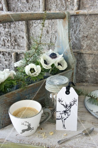 Cup of coffee and tag with picture of stag in front of white anemones in bottle carrier
