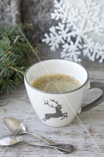 Cup of coffee with grey stag on side next to two silver spoons